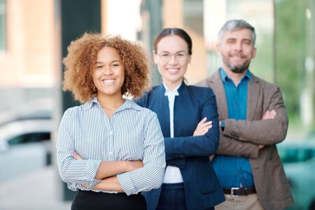 Happy young intercultural leader of contemporary business team in front of row Stock Photo