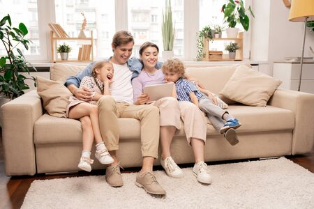 Cheerful kids and their parents in casualwear relaxing on couch in living-room