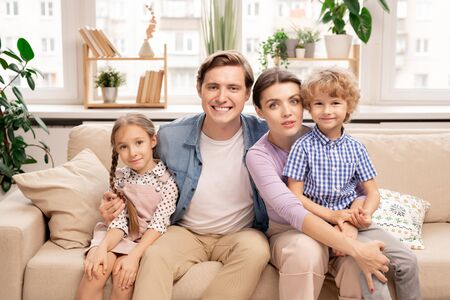 Happy family of four in casualwear sitting on sofa in living-room
