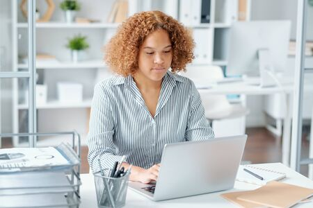 Young mixed-race businesswoman sitting by desk in front of laptop display