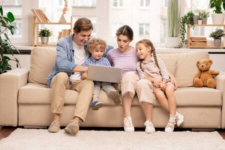 Young family with laptop surfing in the net while choosing movie or cartoons