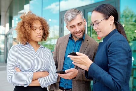 Two young employees with smartphones looking through message history