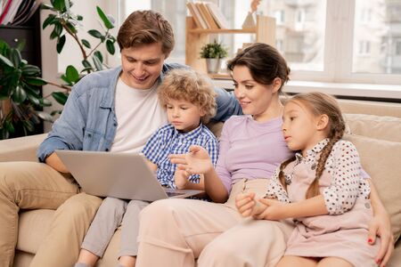 Contemporary couple and two kids discussing movie while watching it at leisure