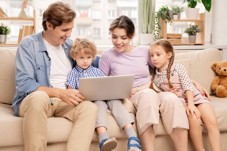 Happy young married man and woman and cute children looking at laptop display 写真素材