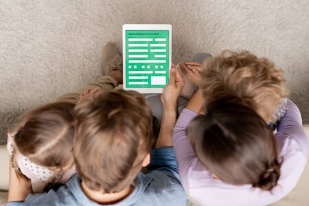 Young family looking at electronic medical form on touchpad display Stock fotó