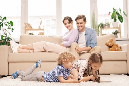 Two cute elementary age kids with touchpad lying on the floor of living-room