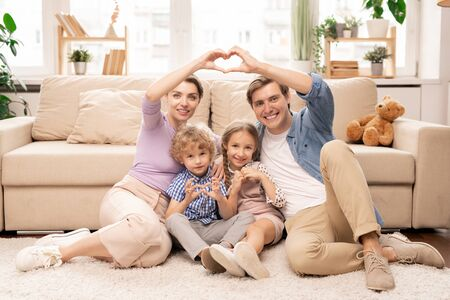 Happy parents and two adorable siblings making heart shape with fingers Stock Photo