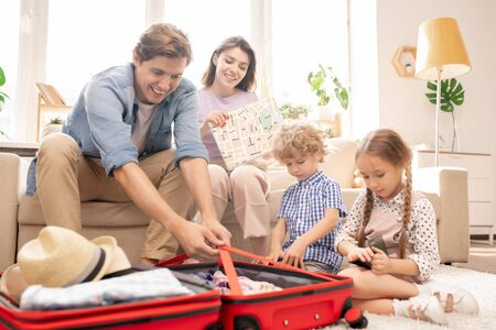 Young couple and two little kids preparing things before travel