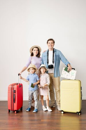 Young casual husband and wife with baggage and their little son and daughter Stock fotó