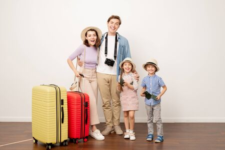 Excited family of two parents and their cute kids in casualwear with suitcases