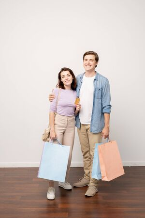 Happy couple of young shoppers with paperbags and credit card standing by wall