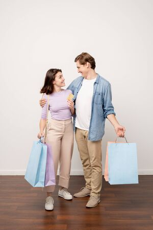 Young affectionate couple in casualwear carrying paperbags after shopping Stock Photo - 129799931