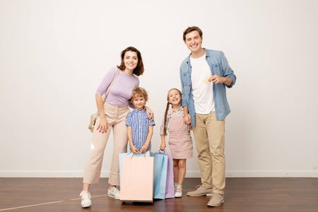 Joyful young parents and their two kids with paperbags looking at you