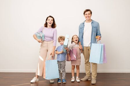 Laughing young parents with paperbags and their cheerful son and daughter