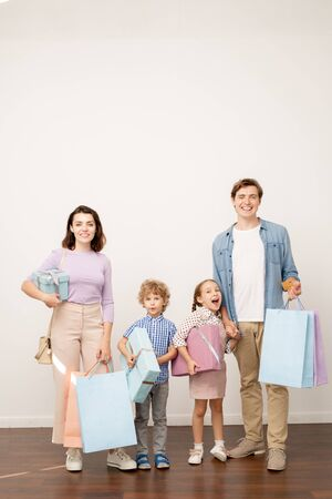 Happy young parents with paperbags and two little kids with giftboxes