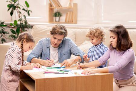 Młoda rodzina małżeństwa i ich dwoje małych dzieci w wieku podstawowym rysuje