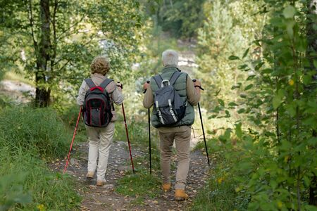 Mature man and woman with trekking sticks moving between green trees and bushes Stock Photo - 129799938