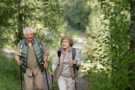 Cheerful mature active couple enjoying trekking in the forest or park Stock Photo - 129799939
