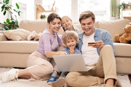 Cheerful family sitting on the floor of living-room and surfing in online shop