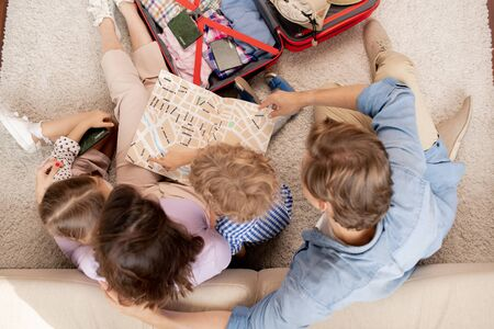 Young family of parents, their son and daughter looking at map guide Stock Photo
