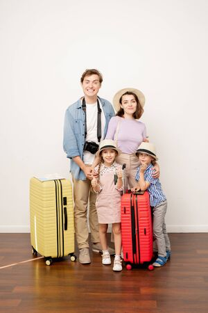 Happy young casual father, mother, son and daughter with baggage in studio