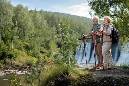 Two happy mature backpackers in activewear standing by forest river