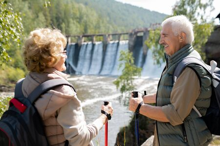 Happy mature man and woman in activewear talking in natural environment on trip