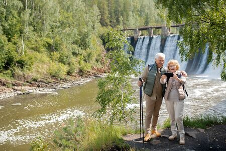 Cheerful senior couple in activewear making selfie on background of waterfalls Stock Photo