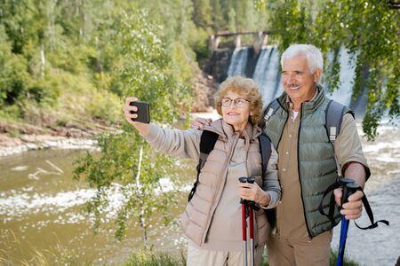 Smiling seniors with trekking sticks making selfie during their trip