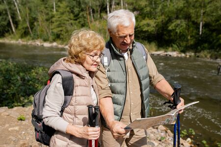 Contemporary seniors in activewear looking at guide map during their trip