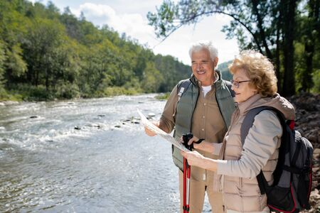 Active senior couple with backpacks looking at map while standing by large river Stock Photo - 129800007