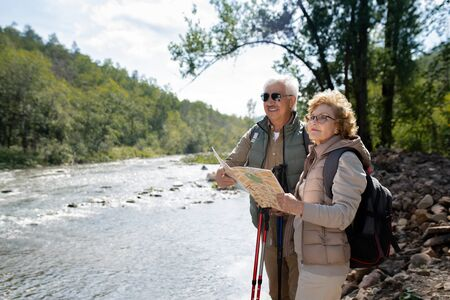 Senior active husband and wife with backpacks and map during trekking trip Stock Photo