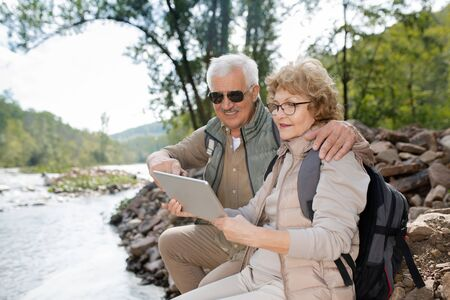 Affectionate senior couple in activewear scrolling in tablet while enjoying trip