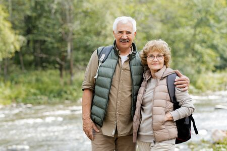 Happy mature male hiker embracing his wife by forest river during trip Stock Photo - 129800014