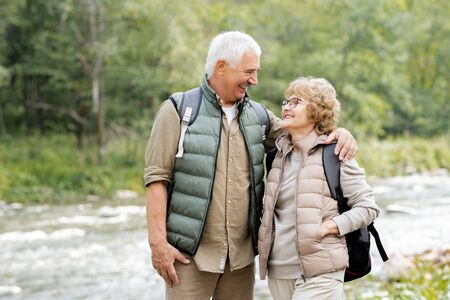 Two cheerful mature backpackers looking at one another in natural environment Stock Photo - 129800049