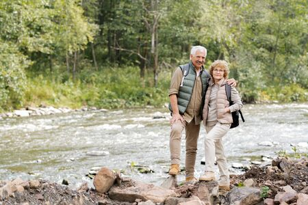 Affectionate mature spouses with backpacks standing on stones on river bank Stock Photo