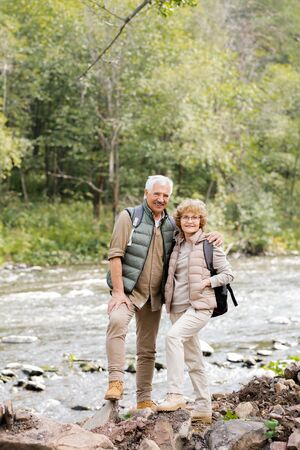 Happy aged active hikers with backpacks looking at you while standing by river Stock Photo - 129800053
