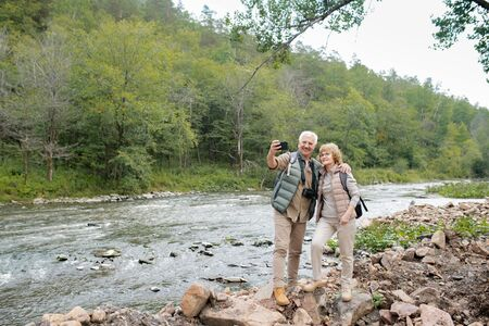 Two cheerful mature hikers with backpacks making selfie on river bank