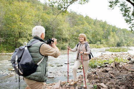 Active female hiker with trekking sticks looking at husband with camera on trip