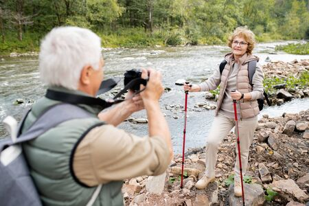 Mature woman with trekking sticks posing for camera held by her husband Stock Photo - 129800051