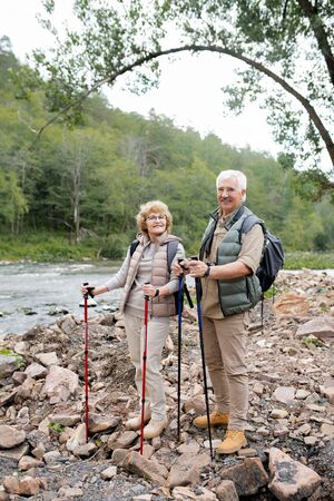 Happy mature man and woman with trekking sticks standing on stones Stock Photo