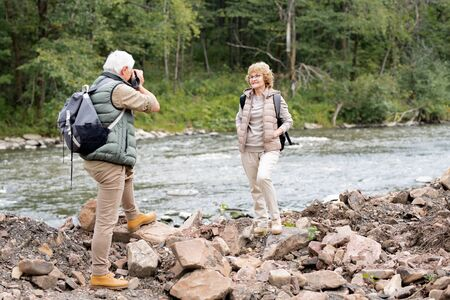 Happy mature female standing by river in front of her husband with camera