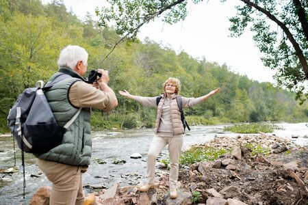 Cheerful aged woman with outstretched arms looking at her husband with camera Stock Photo - 129800058