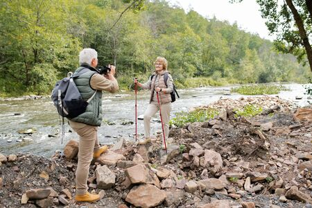 Active mature man with camera photographing his happy wife with trekking sticks Stock Photo - 129800057