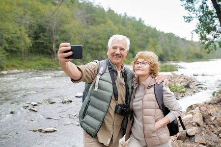 Happy mature active spouses looking at smartphone camera while making selfie