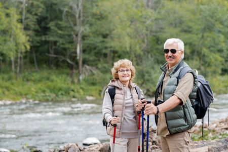 Active aged spouses with backpacks and trekking sticks enjoying summer trip Stock Photo - 129800060