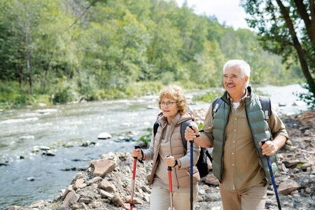 Happy mature hikers with backpacks and trekking sticks walking along riverside Stock Photo