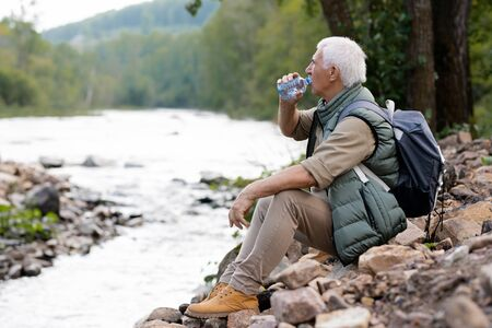 Tired mature backpacker drinking water from plastic bottle on river bank