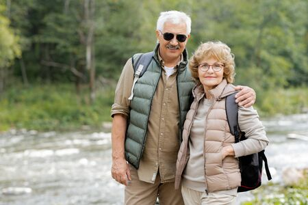 Happy mature active couple with backpacks looking at you by forest river Stock Photo - 129800066