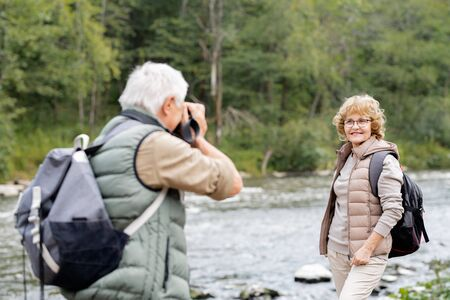 Mature active backpacker photographing his happy wife on river bank